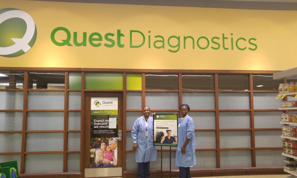 Quest Diagnostics staff stands in front of a banner
