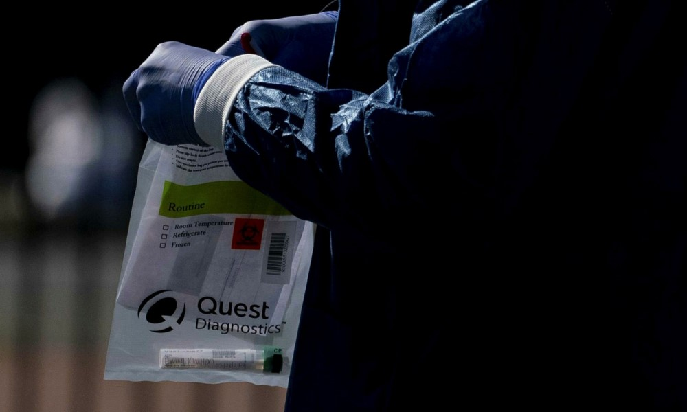 Quest Diagnostics staff collect testing kits
