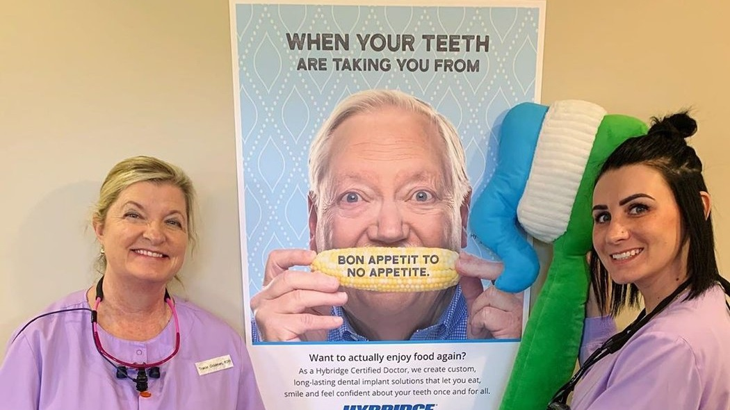 dental hygienist stands next to the banner