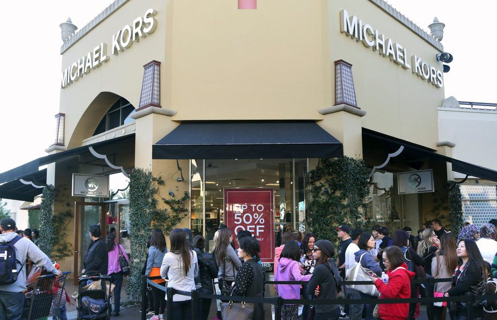 People is shopping at Michael Kors section in Brick and mortar store